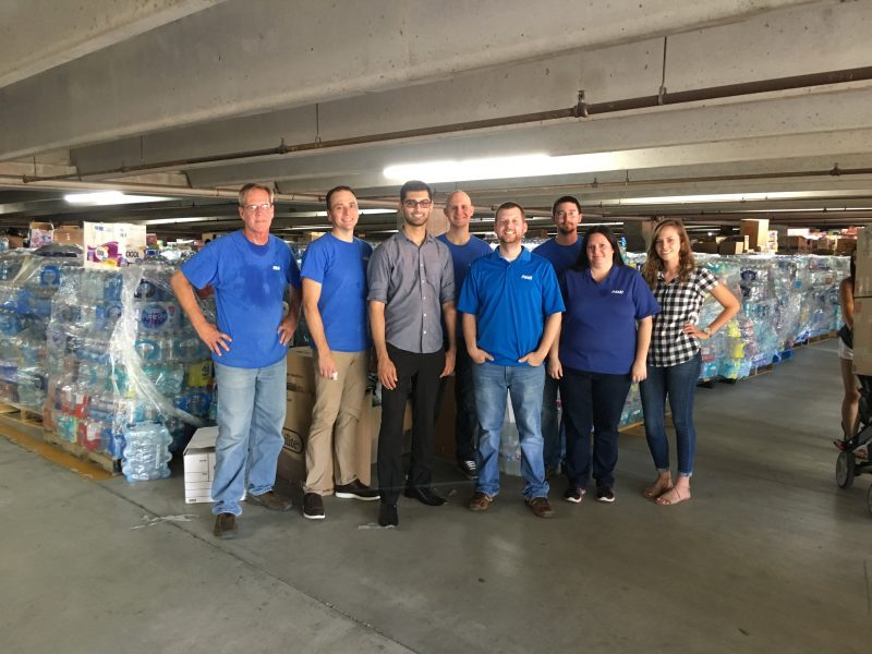 Associates standing with supplies for Hurricane Harvey, Irma relief.