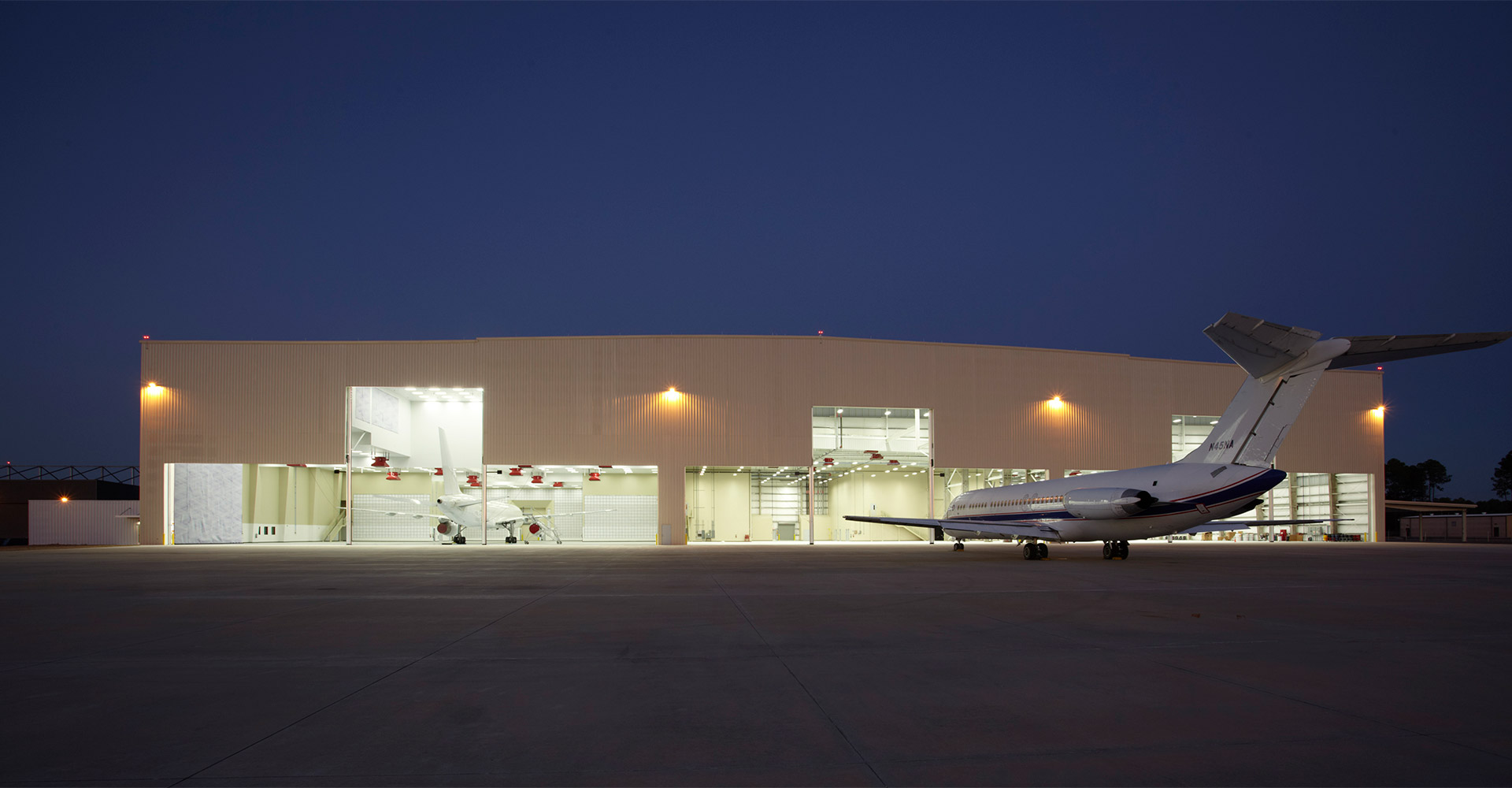 Exterior of FSCJ aircraft service hangar at night.