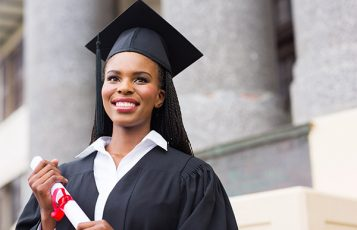Young woman wearing graduation cap and gown.