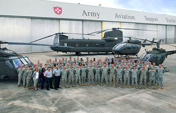 Military members standing in front of helicopters.