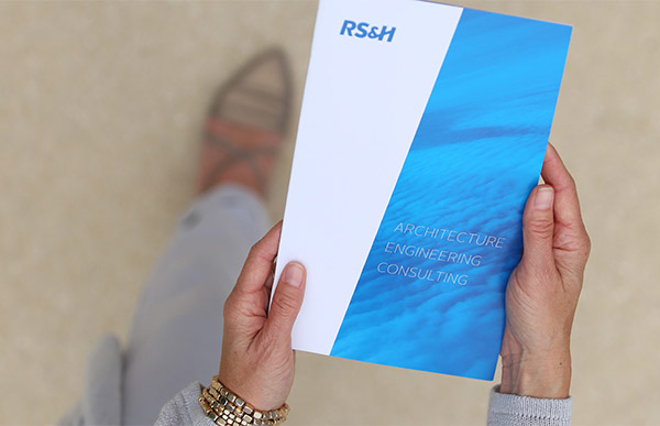 Hands holding RS&H brochure.