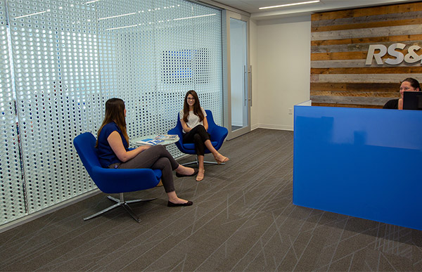 Associates sitting in blue chairs.