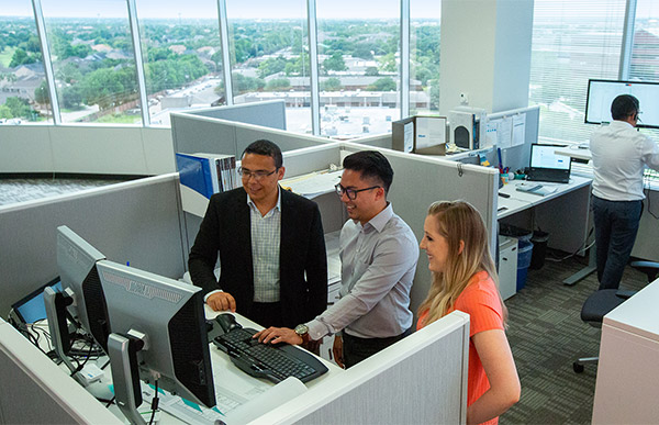 Associates working together around a computer.
