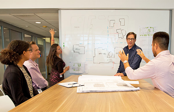 Associates meeting around a white board.