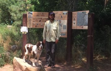 RS&H associate Alan Ross poses with a dog in front of a trail sign in Durango, Colorado.